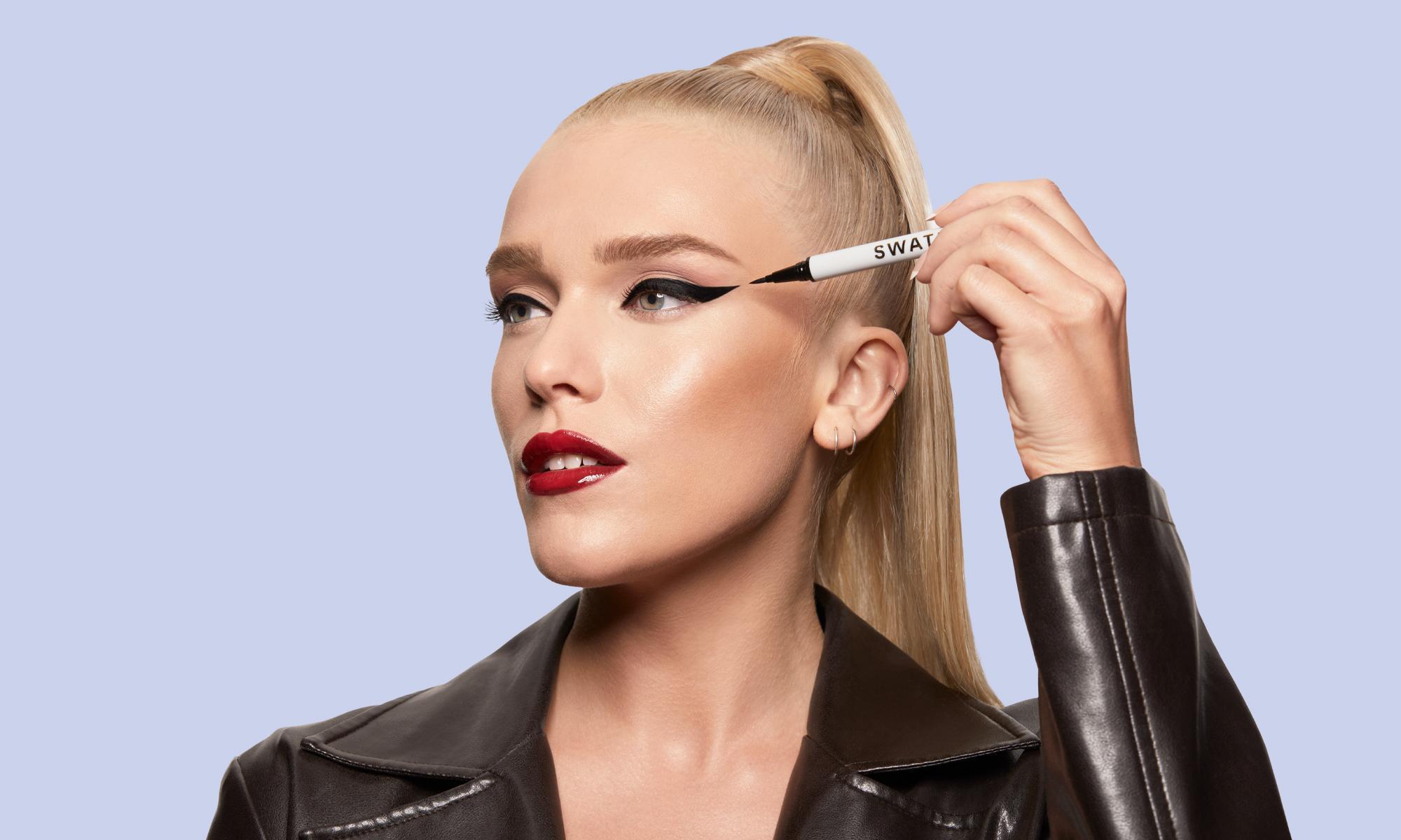 Blonde model applying VANTA Eyeliner from SWATI Glam Kit